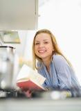 Mujer joven feliz con el libro en cocina Imágenes de archivo libres de regalías