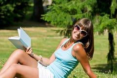 Mujer joven feliz con el libro en parque Imagen de archivo libre de regalías