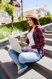 Mujer joven feliz con el limonade que se sienta en las escaleras de la ciudad y que usa el ordenador portátil Fotografía de archivo libre de regalías
