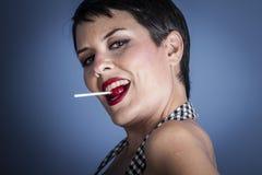 Mujer joven feliz con el lollypop en su boca en fondo azul Imagenes de archivo