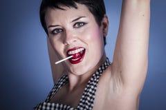 Mujer joven feliz con el lollypop en su boca en fondo azul Foto de archivo