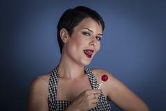 Mujer joven feliz con el lollypop en su boca en fondo azul Fotografía de archivo libre de regalías