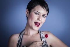 Mujer joven feliz con el lollypop en su boca en fondo azul Imágenes de archivo libres de regalías
