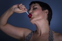 Mujer joven feliz con el lollypop en su boca en fondo azul Fotos de archivo