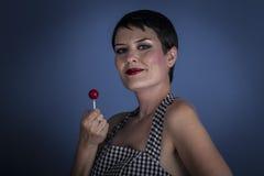 Mujer joven feliz con el lollypop en su boca en fondo azul Imagen de archivo libre de regalías