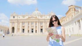 Mujer joven feliz con el mapa de la ciudad en iglesia de la basílica del ` s de la Ciudad del Vaticano y de San Pedro, Roma, Ital almacen de metraje de vídeo