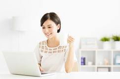 Mujer joven feliz con el ordenador portátil en sala de estar Imágenes de archivo libres de regalías