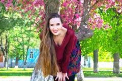 Mujer joven feliz con el pelo largo que sonríe en cámara delante de Sakura Fotografía de archivo libre de regalías
