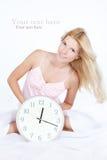 Mujer joven feliz con el reloj en la cama Imagenes de archivo