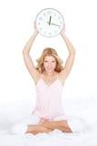 Mujer joven feliz con el reloj en la cama Fotos de archivo libres de regalías