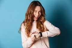 Mujer joven feliz con el reloj a mano que guiña Fotografía de archivo
