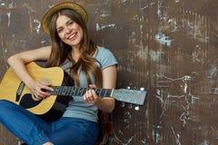 Mujer joven feliz con el sombrero que se sienta con la guitarra acústica en grun Imagen de archivo libre de regalías
