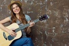 Mujer joven feliz con el sombrero que se sienta con la guitarra acústica en grun Fotos de archivo libres de regalías