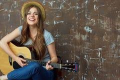 Mujer joven feliz con el sombrero que se sienta con la guitarra acústica en grung Foto de archivo libre de regalías