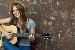 Mujer joven feliz con el sombrero que se sienta con la guitarra acústica en grung Imagenes de archivo