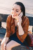 Mujer joven feliz con hablar y la risa en el teléfono elegante del teléfono elegante en un parque de la ciudad que se sienta en u imagenes de archivo