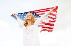 Mujer joven feliz con la bandera americana al aire libre Imagenes de archivo