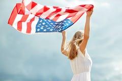 Mujer joven feliz con la bandera americana al aire libre Foto de archivo libre de regalías