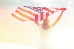 Mujer joven feliz con la bandera americana al aire libre Foto de archivo