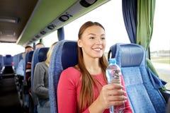Mujer joven feliz con la botella de agua en autobús del viaje Fotografía de archivo