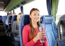 Mujer joven feliz con la botella de agua en autobús del viaje Fotos de archivo