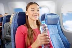 Mujer joven feliz con la botella de agua en el avión fotos de archivo