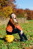 Mujer joven feliz con la calabaza que se sienta al aire libre el día del otoño Imágenes de archivo libres de regalías
