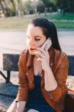 Mujer joven feliz con la chaqueta de cuero que habla y que escucha en el teléfono elegante del teléfono elegante en un parque de  fotografía de archivo