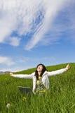 Mujer joven feliz con la computadora portátil imagenes de archivo