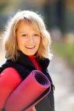 Mujer joven feliz con la estera de la yoga imagenes de archivo