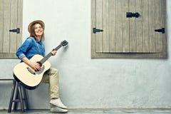 Mujer joven feliz con la guitarra Imagen de archivo libre de regalías