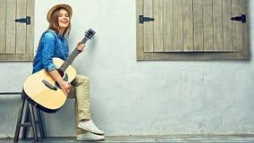 Mujer joven feliz con la guitarra Imágenes de archivo libres de regalías