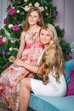 Mujer joven feliz con la hija adolescente linda que se sienta en el sofá en el hom Imagenes de archivo