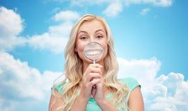 Mujer joven feliz con la lupa Imagen de archivo libre de regalías