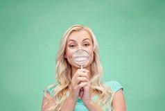 Mujer joven feliz con la lupa Imagenes de archivo