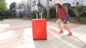 Mujer joven feliz con la maleta roja que llega al centro turístico o al apartamento metrajes