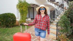 Mujer joven feliz con la maleta roja que llega al centro turístico o al apartamento almacen de metraje de vídeo
