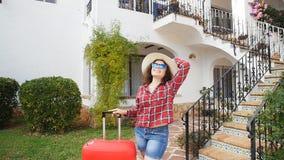 Mujer joven feliz con la maleta roja que llega al centro turístico o al apartamento almacen de video