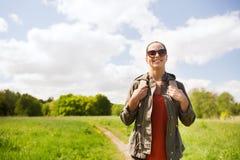 Mujer joven feliz con la mochila que camina al aire libre Foto de archivo