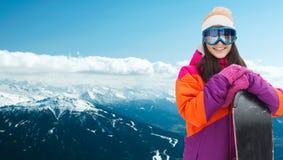 Mujer joven feliz con la snowboard sobre las montañas Foto de archivo