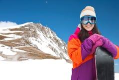 Mujer joven feliz con la snowboard sobre las montañas Fotos de archivo libres de regalías