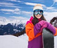 Mujer joven feliz con la snowboard sobre las montañas Fotografía de archivo