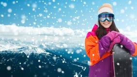 Mujer joven feliz con la snowboard sobre las montañas Imagen de archivo libre de regalías
