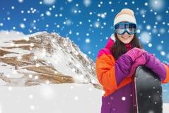 Mujer joven feliz con la snowboard sobre las montañas Imagen de archivo