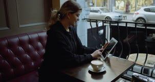 Mujer joven feliz con la tableta en café 4K almacen de video