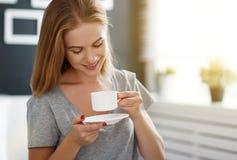 Mujer joven feliz con la taza de café de la mañana en cama Foto de archivo libre de regalías