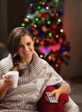 Mujer joven feliz con la taza de chocolate caliente que ve la TV Fotos de archivo