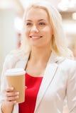 Mujer joven feliz con la taza de papel del café en alameda Fotografía de archivo