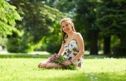 Mujer joven feliz con las flores en parque del verano Imagen de archivo