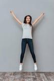 Mujer joven feliz con las manos aumentadas que saltan en el aire Fotos de archivo libres de regalías